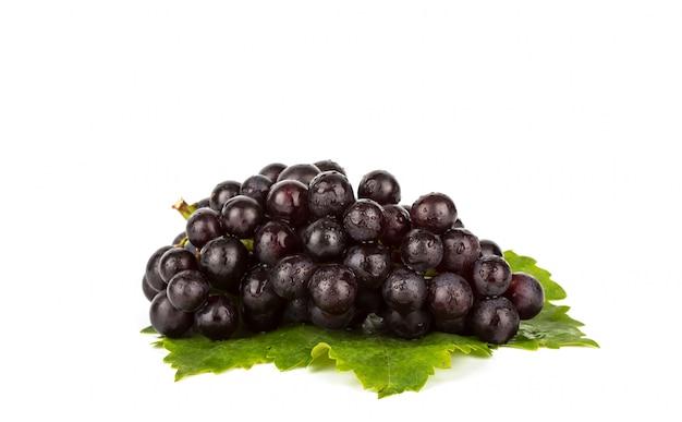 Rode druif met groen blad op een witte achtergrond