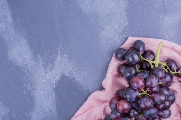 Rode druiven bessen geïsoleerd op blauwe tafel. Gratis Foto