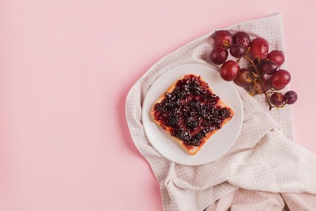 Rode druiven en boterham met jam op witte plaat over het tafelkleed tegen roze achtergrond