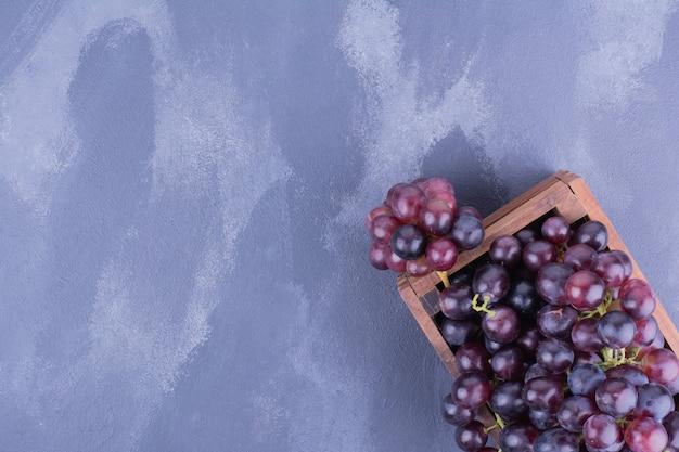 Rode druiven in een houten bakje op blauwe ondergrond
