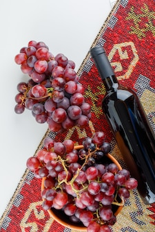 Rode druiven in een kom met wijn bovenaanzicht op wit en traditioneel tapijt