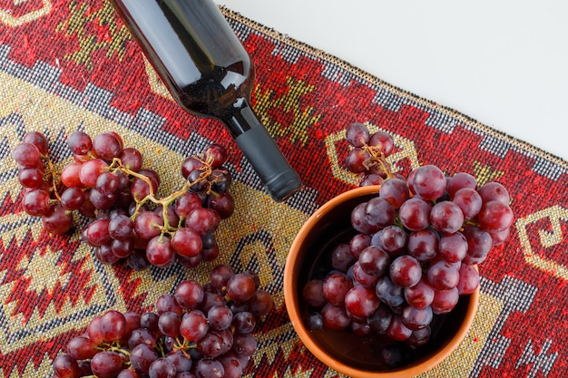 Rode druiven in een kom met wijn plat leggen op wit en traditioneel tapijt