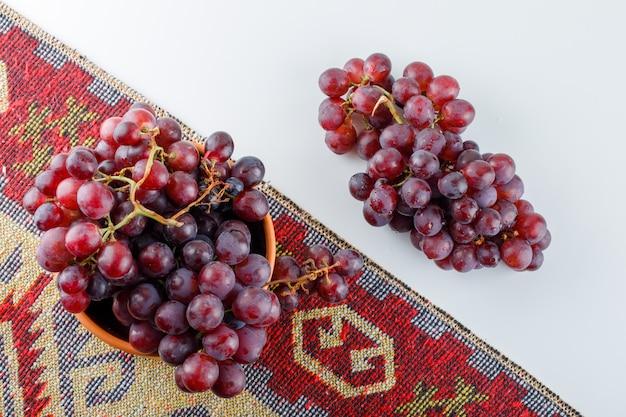 Rode druiven in een kom plat lag op wit en traditioneel tapijt