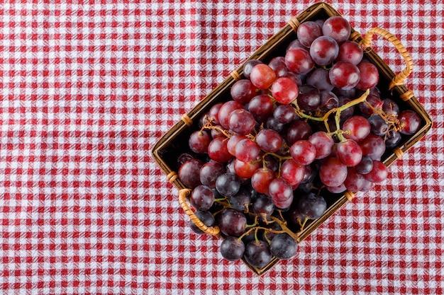 Rode druiven in een mand op picknickdoek,