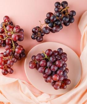 Rode druiven in een plaat op roze en textiel.