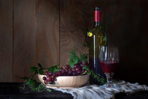 Rode druiven met een glas wijn en een fles op hout.