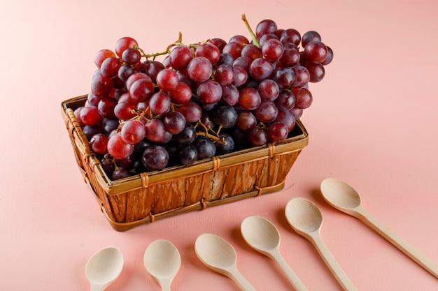 Rode druiven met houten lepels in een mand op roze, hoge hoekmening.