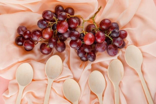 Rode druiven met houten lepels plat leggen op een roze textiel