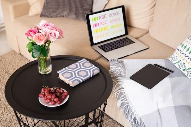 Rode druiven op schotel, roze rozen in glas water en boek op kleine tafel door bank met laptop, stootkussen en stylus in huiskamer