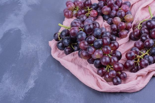 Rode druivenbossen op stuk van roze handdoek.
