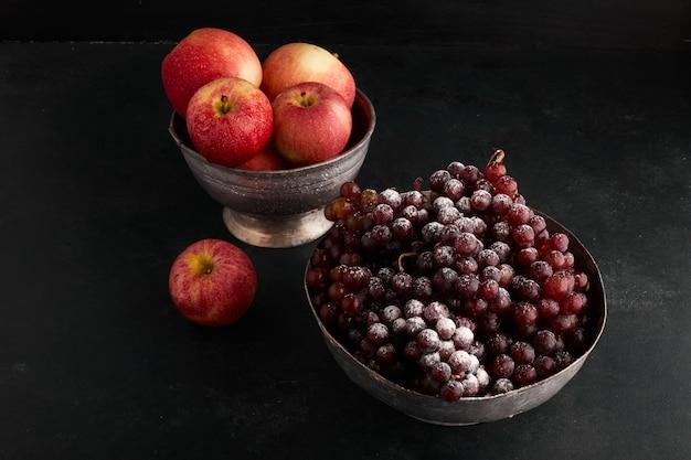 Rode druiventrossen en appels in metalen bekers.