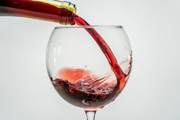 Rode druivenwijn stroomt uit de hals van de fles in een wijnglas op een witte achtergrond