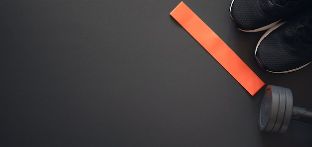 Rode elastische rubberen band, sportschoenen en halter op zwart. plat leggen