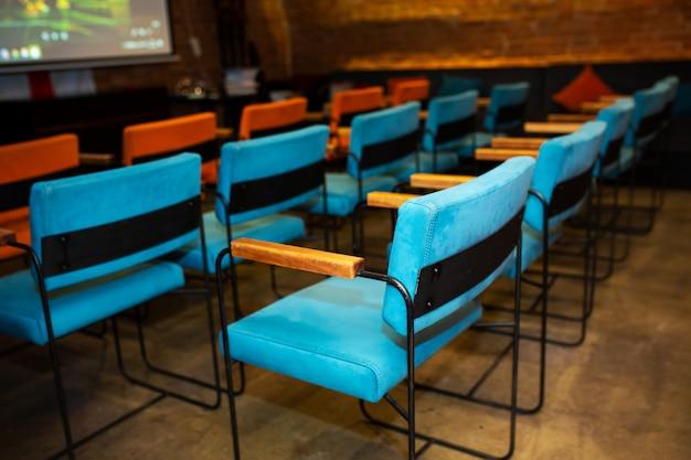 Rode en blauwe stoelen in de donkere hal van een kleine bioscoop