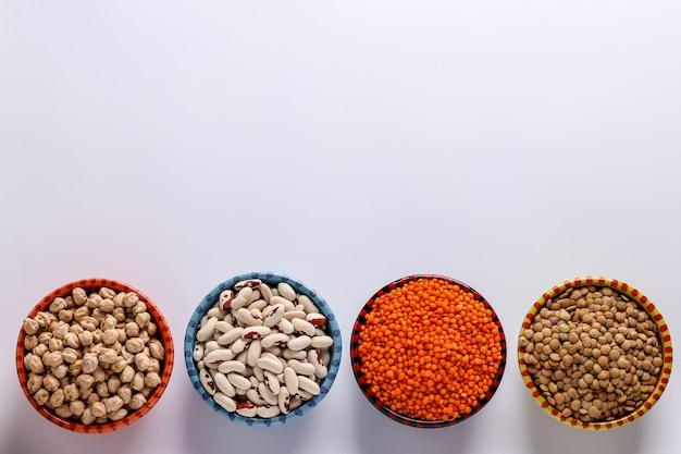 Rode en bruine linzen, kikkererwten en witte bonen zijn peulvruchten die veel eiwitten bevatten, bevinden zich op een witte achtergrond in kommen, horizontale oriëntatie, kopieerruimte