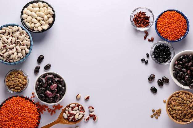 Rode en bruine linzen, zwarte, bruine en witte bonen zijn peulvruchten die veel eiwitten bevatten, bevinden zich in kommen op een wit oppervlak, horizontale oriëntatie, kopieerruimte