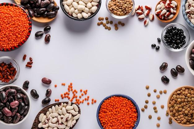 Rode en bruine linzen, zwarte, bruine en witte bonen zijn peulvruchten die veel eiwitten bevatten en bevinden zich in kommen op een witte achtergrond