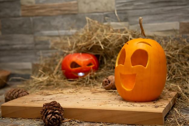 Rode en gele halloween-pompoenen liggen op het hooi kegels van dennenboom liggen in de buurt van board jack o lanterns