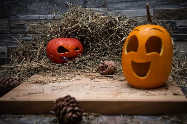 Rode en gele halloween-pompoenen liggen op het hooi kegels van dennenboom liggen in de buurt van bord