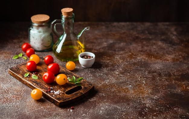 Rode en gele kerstomaatjes, een fles olijfolie, zout, peper en basilicum