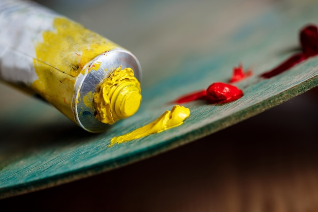 Rode en gele olieverf op palet over houten muur
