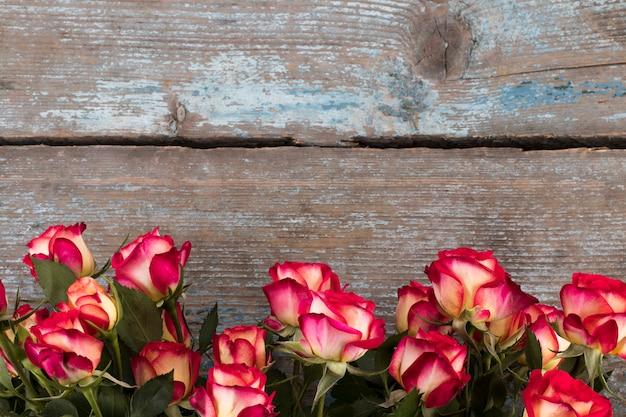 Rode en gele rozen op houten, exemplaarruimte