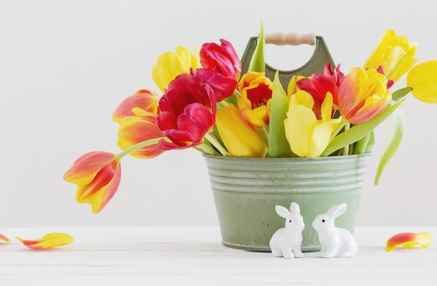 Rode en gele tulpen in emmer en ceramisch konijn op witte achtergrond