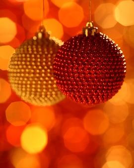 Rode en gouden kerstboomversieringen tegen onscherpe achtergrond