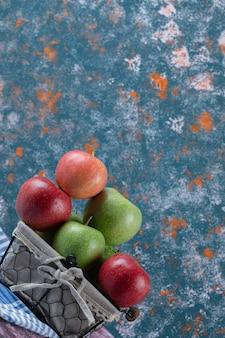 Rode en groene appels in een rustieke mand