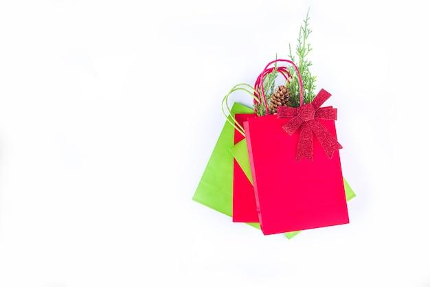 Rode en groene boodschappentassen met kerstversiering, sparren takken, feestelijke boog geïsoleerd op een witte achtergrond bovenaanzicht kopie ruimte. kerst verkoop concept