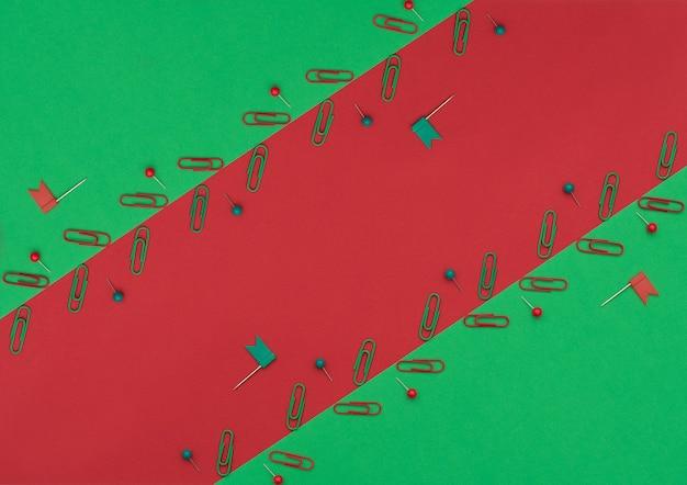 Rode en groene clips en pinnen op dubbele groene en rode achtergrond. school- en kantoorbenodigdheden.