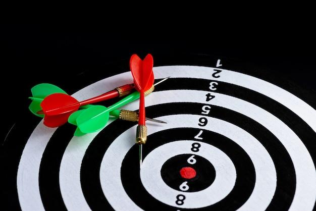 Rode en groene dartpijl die doelcentrum raakt