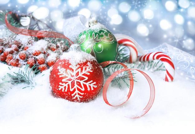 Rode en groene kerstversiering op sneeuw, kopie ruimte