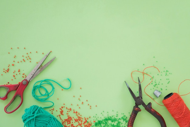 Rode en groene kralen; schaar; tangen en spoel op groene achtergrond
