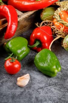 Rode en groene paprika's op een rustieke achtergrond.