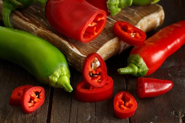 Rode en groene paprika's op houten achtergrond