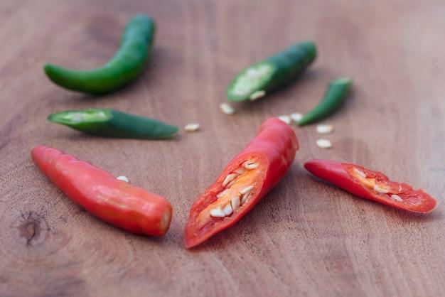 Rode en groene pepers worden afwisselend op een houten snijplank gelegd