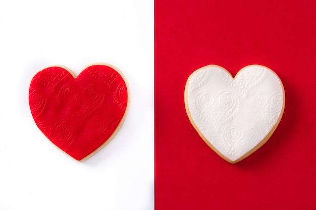 Rode en hartvormige koekjes voor valentijnsdag op witte en rode ondergrond