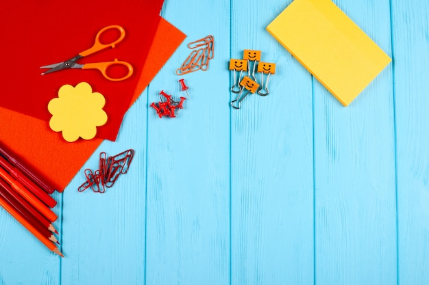 Rode en oranje kantoorbehoeften op blauwe houten achtergrond.
