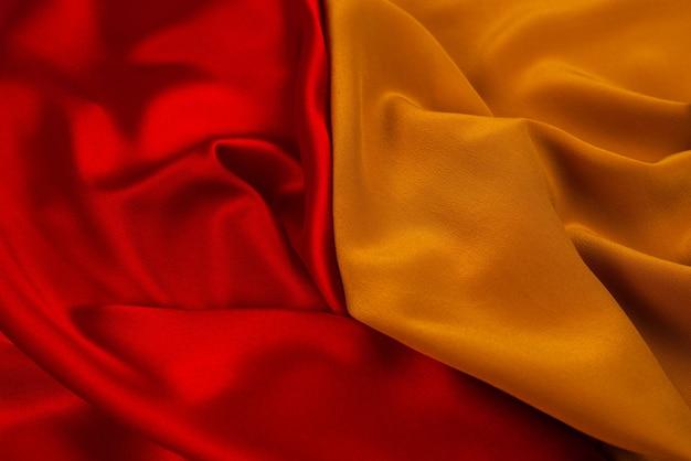 Rode en oranje zijde of satijn luxe stoffentextuur kan als abstracte muur worden gebruikt. bovenaanzicht.