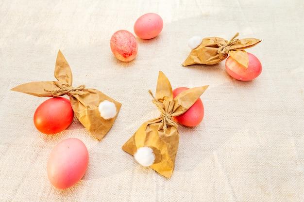 Rode en roze eieren voor pasen met papieren konijntjes