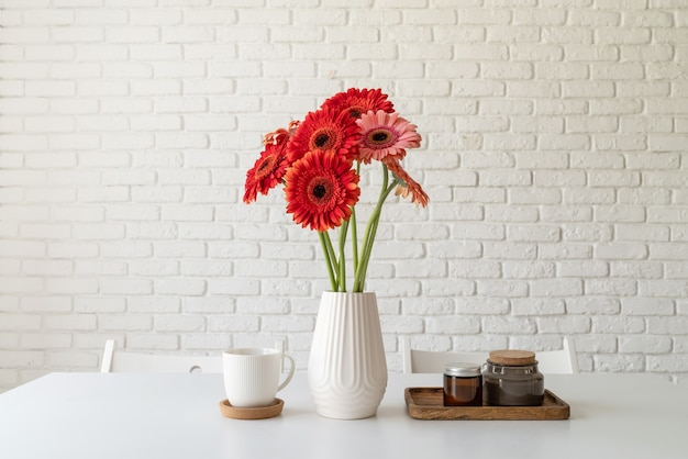 Rode en roze gerbera madeliefjes in witte vaas op keukentafel en witte bakstenen muur