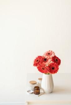 Rode en roze gerbera madeliefjes in witte vaas op keukentafel en witte muur achtergrond