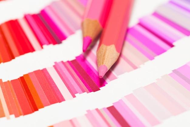 Rode en roze kleurpotloden en kleurenkaart van alle kleuren