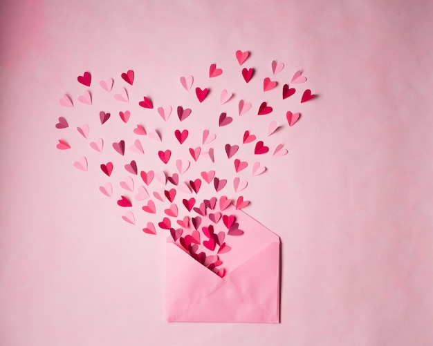 Rode en roze papieren harten in open roze postenvelop op roze