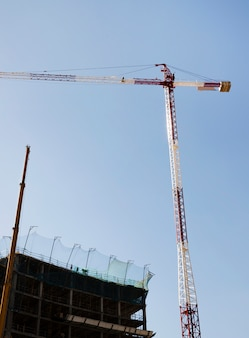 Rode en witte bouwkraan voor de bouw tegen blauwe hemel