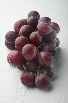 Rode en witte druiven set, donkerrood fruit, op witte stenen tafel