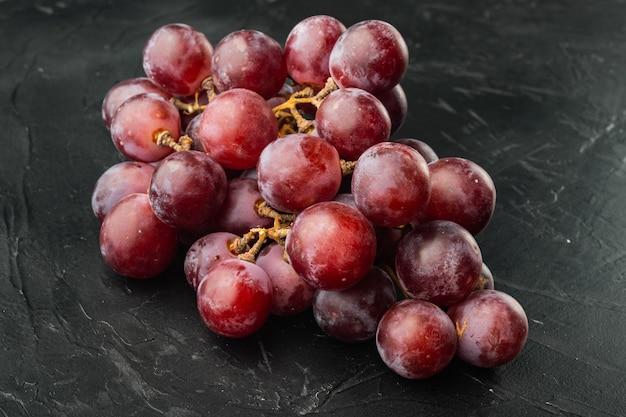 Rode en witte druiven set, donkerrood fruit, op zwarte stenen tafel