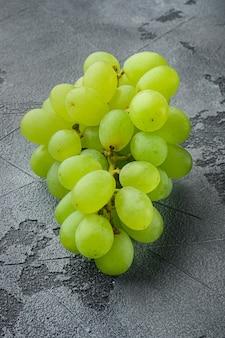 Rode en witte druiven set, groen fruit, op grijze stenen tafel