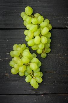 Rode en witte druiven set, groen fruit, op zwarte houten tafel, bovenaanzicht plat lag